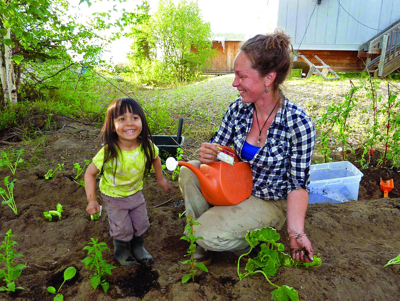 A young gardener provides entertainment while Linnea transplants Johanna Tickett's garden in Shungnak. (photo by Seth Kantner)